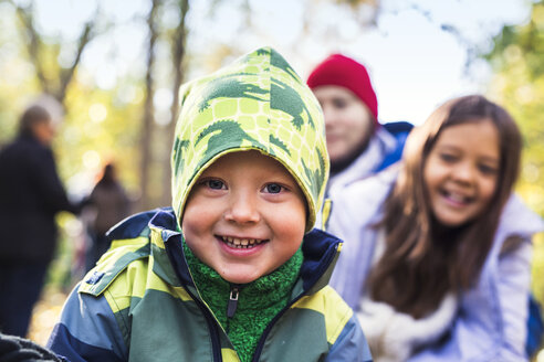 Portrait of happy boy wearing warm clothing with family in background at forest - ASTF04611