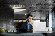 Businessman using laptop while sitting at restaurant - ASTF04650