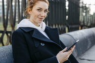 Portrait of smiling young woman sitting on a bench holding cell phone - JRFF02674