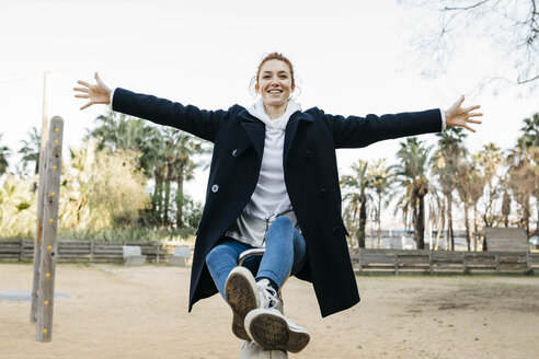 Portrait of happy young woman on a seesaw on playground - JRFF02677