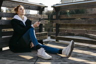 Young woman resting outdoors holding cell phone - JRFF02683