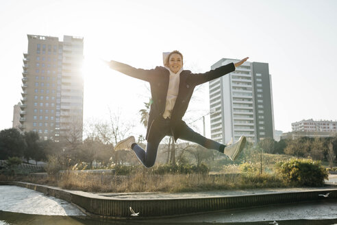 Happy young woman jumping in a park with the city in background - JRFF02686