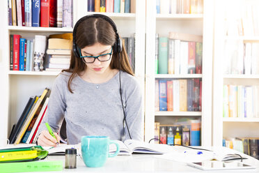 Girl listening music with headphones while doing homeworks - LVF07825