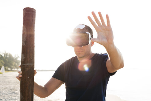 Man with wood pole wearing VR glasses on the beach - HMEF00220