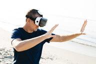 Man wearing VR glasses on the beach - HMEF00223