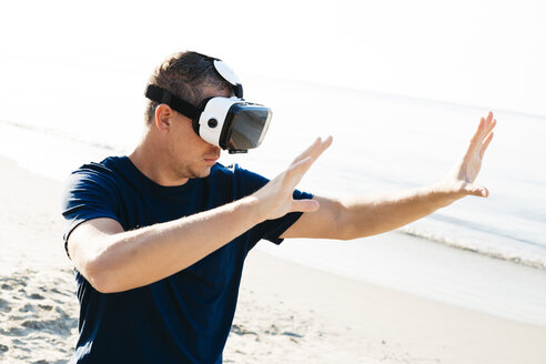 Man wearing VR glasses on the beach - HMEF00223