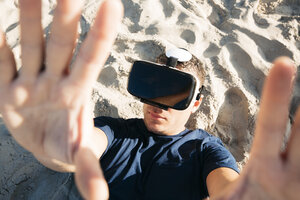 Man wearing VR glasses lying in sand on the beach - HMEF00226