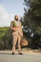 Man wearing suit with colourful polka-dots standing on country road with travelling bag and potted plant - KBF00508