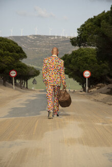 Back view of bald man wearing suit with colourful polka-dots walking on country road with travelling bag - KBF00511