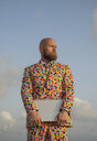 Portrait of bald man with beard  wearing suit with colourful polka-dots holding laptop - KBF00523