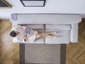 Mature woman in bathrobe sitting on the couch at home using digital tablet - PSIF00244
