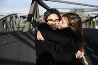Happy friends hugging each other on a bridge - IGGF00809