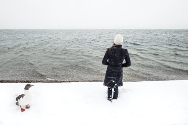 Grey goose and young woman at Lake Starnberg in winter - WFF00004