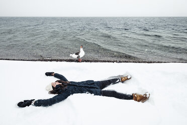 Grey goose and young woman at Lake Starnberg in winter - WFF00007