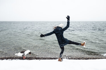 Grey goose and young woman at Lake Starnberg in winter - WFF00010