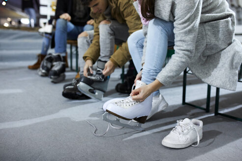 Friends putting on ice skates at an ice rink - ZEDF01872