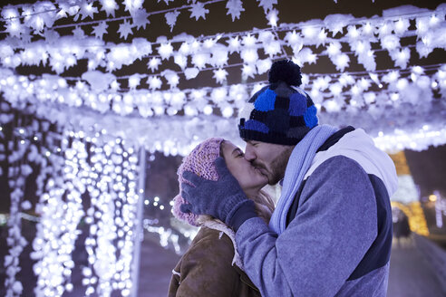 Happy young couple kissing in winter decoration - ZEDF01875