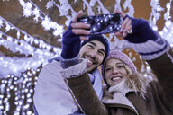Happy young couple in winter decoration taking a selfie - ZEDF01878
