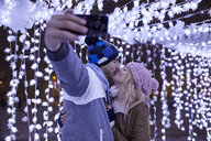 Young couple in winter decoration kissing and taking a selfie - ZEDF01881