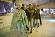 Happy friends ice skating on an ice rink at night - ZEDF01890