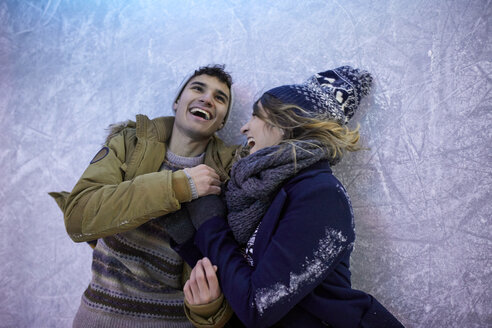 Laughing couple lying on an ice rink at night - ZEDF01896