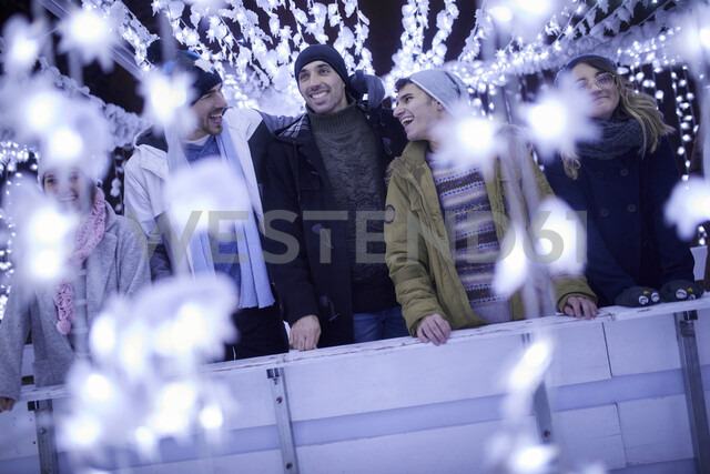 Happy friends standing in festive Christmas decoration at night - ZEDF01902