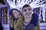 Happy young couple hugging in winter decoration - ZEDF01905