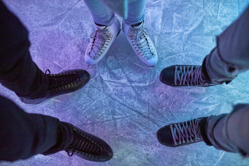 Legs of friends wearing ice skates standing on an ice rink - ZEDF01917