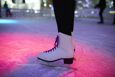 Leg of woman wearing ice skates standing on an ice rink - ZEDF01920