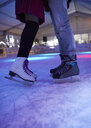 Legs of couple wearing ice skates standing on an ice rink - ZEDF01923