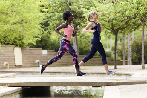 Two sporty young women running together in a park - JSRF00128