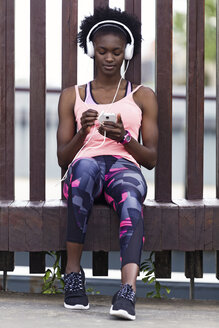 Lleida, Catalonia, Spain,Shot of sporty young woman listening to music with smartphone after running in the city. - JSRF00131