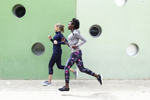Two sporty young women running together in the city passing wall with round windows - JSRF00137