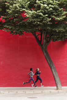 Two sporty young women running together in the city passing red wall - JSRF00140