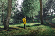 Girl wearing yellow raincoat and yellow backpack standing on a meadow - ERRF00770