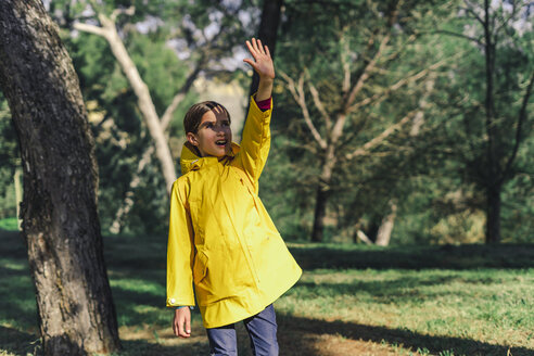 Girl wearing yellow raincoat standing at sunlight shielding eyes with her hand - ERRF00773