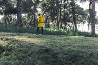 Girl wearing yellow raincoat and yellow backpack walking in nature - ERRF00776