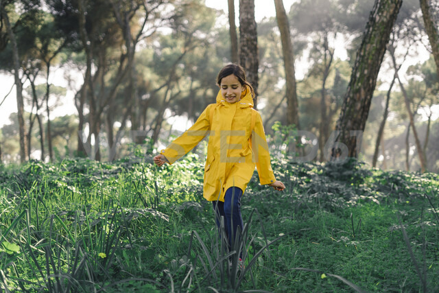 Smiling girl wearing yellow raincoat and walking in the woods - ERRF00779 - Eloisa Ramos/Westend61