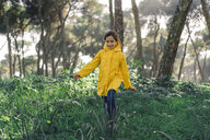 Smiling girl wearing yellow raincoat and walking in the woods - ERRF00779