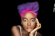 Portrait of eccentric young woman with pink and purple dyed hair in front of black background - DMOF00137