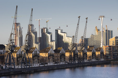 UK, London, Docklands, renovated residential buildings and harbor cranes, gondolas of the Emirates cable car - WIF03824