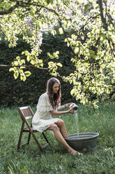 Young woman wearing white dress preparing footbath in garden - WFF00011