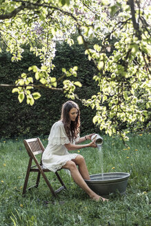 Young woman wearing white dress preparing footbath in garden - WFF00011