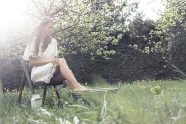Young woman wearing white dress sittiing in garden taking footbath - WFF00014