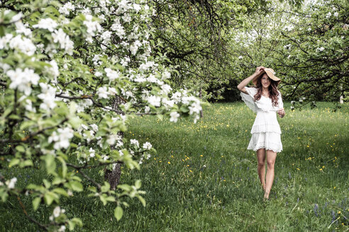Young woman wearing white dress and floppy hat walking barefoot in garden with blossoming apple trees - WFF00017