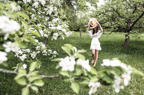 Young woman wearing white dress and floppy hat walking barefoot in garden with blossoming apple trees - WFF00020