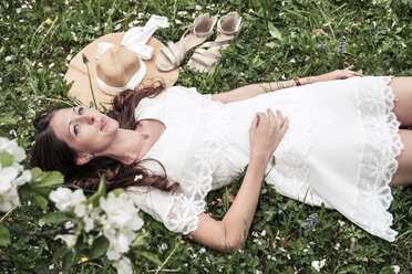 Portrait of daydreaming young woman wearing white lace dress lying on flower meadow - WFF00026
