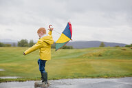 Redheaded little boy with umbrella playing in the rain - NMS00299