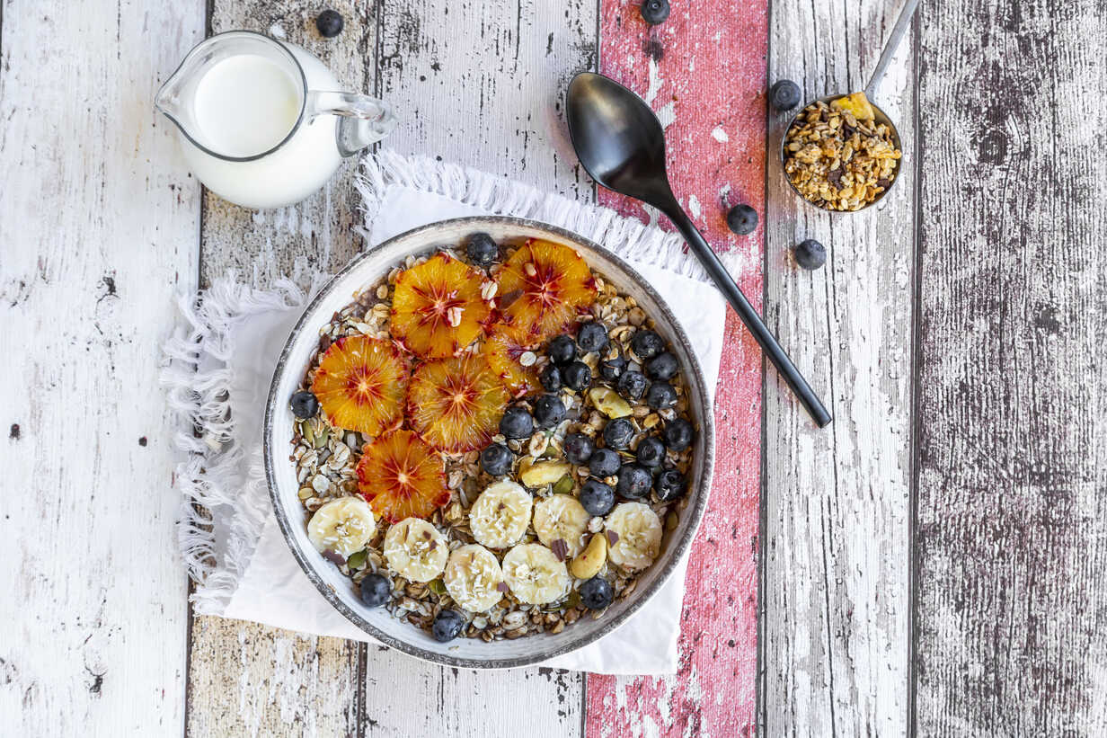 Cereals with banana, blueberries, blood orange, coconut flakes and milk - SARF04122 - Sandra Roesch/Westend61