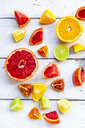 Sliced citrus fruits on white wood - SARF04128